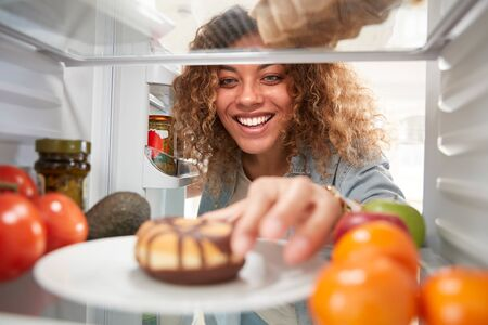 View Looking Out From Inside Of Refrigerator As Woman Opens Door And Reaches For Unhealthy Donut