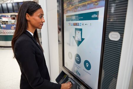 Businesswoman Commuting To Work Buying Train Ticket From Self Service Machine