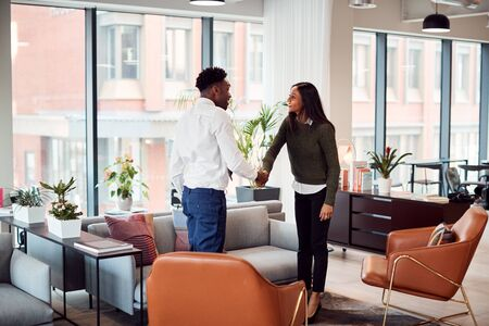 Businesswoman Shaking Hands With Male Interview Candidate In Seating Area Of Modern Office