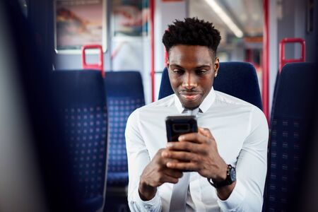 Businessman Sitting In Train Commuting To Work Checking Messages On Mobile Phone