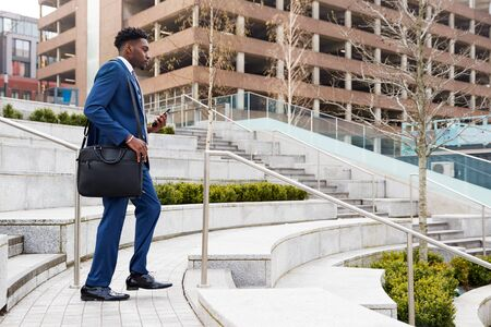 Businessman Commuting To Work Walking Down Steps To Railway Station
