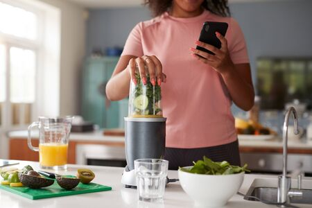Close Up Of Woman Using Fitness Tracker To Count Calories For Post Workout Juice Drink She Is Making Zdjęcie Seryjne