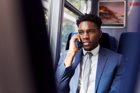 Businessman Sitting In Train Commuting To Work Making Call On Mobile Phone