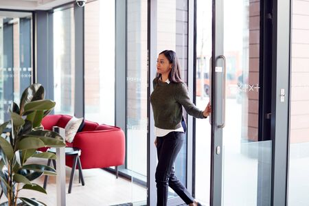 Businesswoman Arriving For Work At Office Walking Through Door