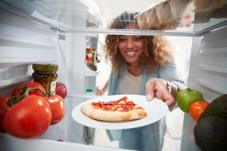 View Looking Out From Inside Of Refrigerator As Woman Opens Door For Leftover Takeaway Pizza Slice Zdjęcie Seryjne