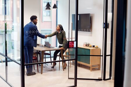 Businesswoman Shaking Hands With Male Job Candidate In Meeting Room After Interview Zdjęcie Seryjne