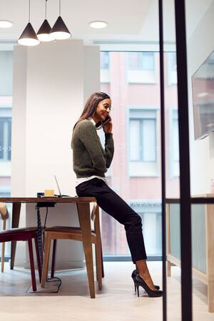 Businesswoman Sitting On Desk In Meeting Room Talking On Mobile Phone
