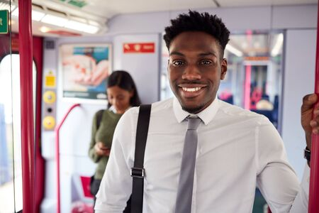 Portrait Of Smiling Businessman Standing In Train Commuting To Work