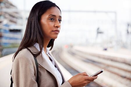 Businesswoman Standing On Railway Platform Commuting To Work Booking Ticket On Mobile Phone