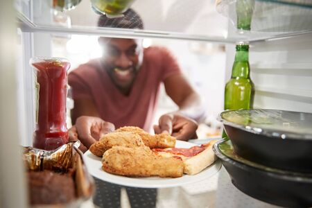 View Looking Out From Inside Of Refrigerator Filled With Unhealthy Takeaway Food As Man Opens Door