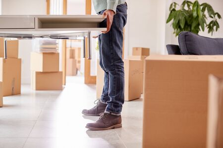 Close Up Of Couple In New Home On Moving Day Carrying Table Together