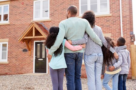 Rear View Of Family Standing Outside New Home On Moving Day Looking At House Zdjęcie Seryjne