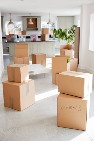 Stacked Removal Boxes In Empty Room On Moving Day