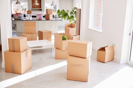 Gestapelde verhuisdozen in lege ruimte op verhuisdag Stockfoto