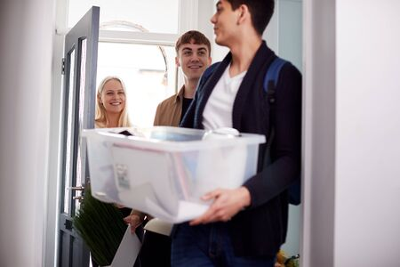 Group Of College Student Carrying Boxes Moving Into Accommodation Together Imagens