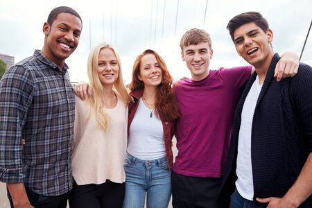 Portrait Of Student Friends Walking Across Bridge In City Together Stock Photo