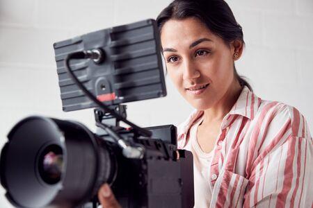 Weibliche Videografin mit Videokamera filmt im weißen Studio