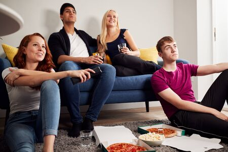 Group Of College Students In Shared House Watching TV And Eating Pizza Stock Photo