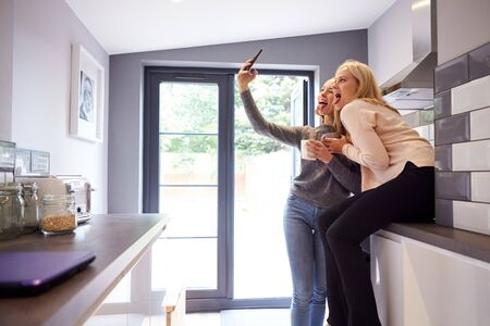 Two Female College Students Taking Selfie In Rented House Kitchen