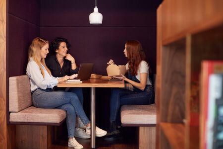 Group Of Young Businesswomen Sitting Around Table In Modern Workspace Having Working Lunch Meeting Stock Photo