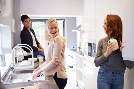 Group Of College Student Friends In Shared House Kitchen Washing Up And Hanging Out Together