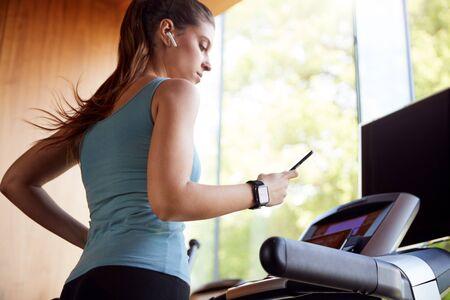 Femme exerçant sur un tapis roulant portant des écouteurs sans fil et une montre intelligente vérifiant le téléphone portable