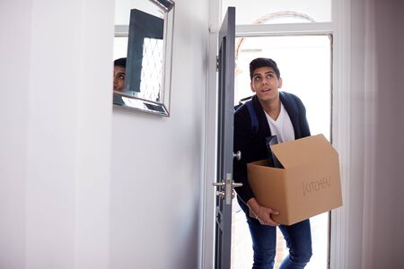 Male College Student Carrying Box Moving Into Accommodation