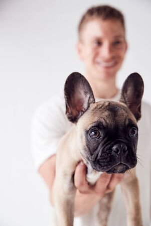 Studio Portrait Of Smiling Young Man Holding Pet French Bulldog Puppy Stock Photo