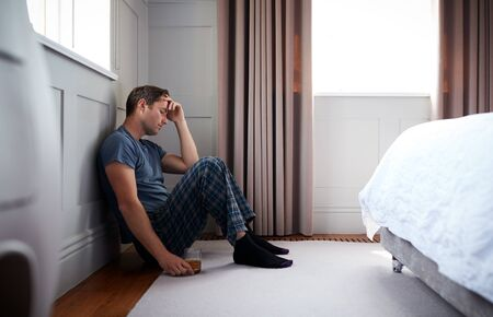 Depressed Man Wearing Pajamas Sitting On Floor Of Bedroom Holding Glass Of Whisky Фото со стока