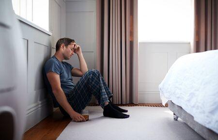 Depressieve man met pyjama zittend op de vloer van de slaapkamer met een glas whisky Whisk