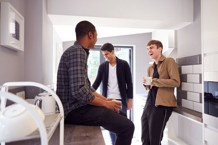 Group Of Male College Students In Shared House With Hot Drinks In Kitchen Hanging Out Together