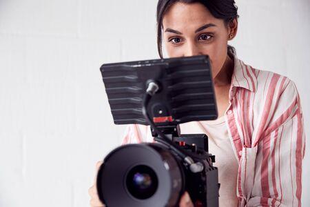 Videógrafo femenino con cámara de vídeo filmando películas en White Studio Foto de archivo