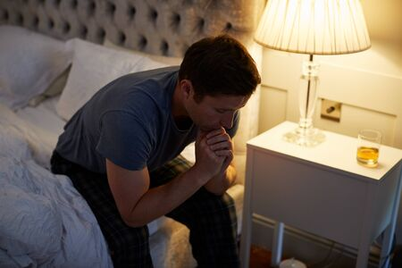 Depressed Man Wearing Pajamas Sitting On Side Of Bed With Glass Of Whisky On Bedside Cabinet