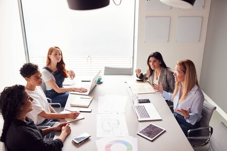 Team Of Young Businesswomen In Meeting Around Table In Modern Workspace Stock Photo