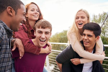 Student Friends With Men Giving Women Piggyback Rides Across City Bridge