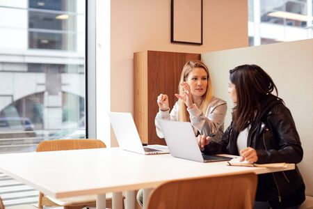 Two Young Businesswomen In Meeting Around Table In Modern Open Plan Workspace Stock Photo