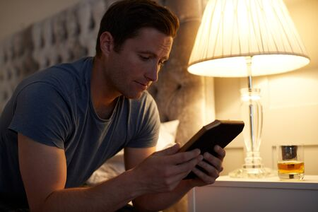 Sad Man Looking At Photo Sitting On Side Of Bed With Glass Of Whisky On Bedside Cabinet Фото со стока