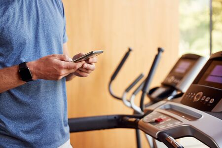Close Up Of Man Exercising On Treadmill At Home Wearing Smart Watch Checking Mobile Phone