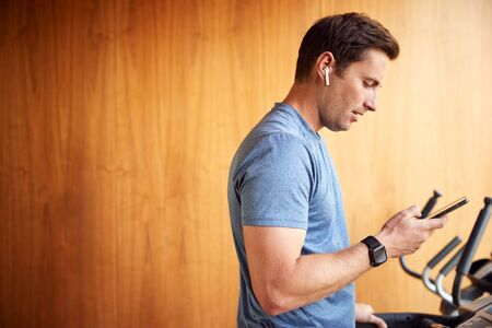 Man Exercising On Treadmill At Home Wearing Wireless Earphones Checking Mobile Phone 免版税图像