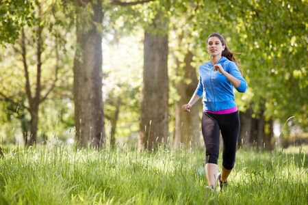 Young Woman Exercising Running Through Countryside Field Stock fotó