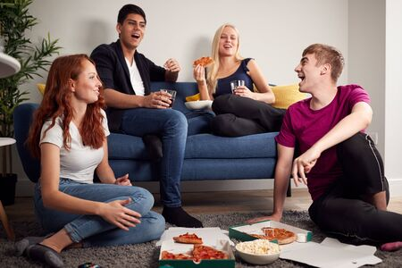 Group Of College Students In Shared House Having Night In Eating Pizza Together
