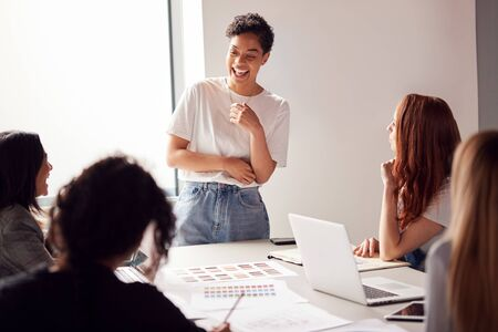 Female Boss Gives Presentation To Team Of Young Businesswomen Meeting Around Table In Modern Office