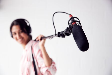 Portrait Of Female Sound Recordist Holding Microphone On Video Film Production In White Studio Stock fotó