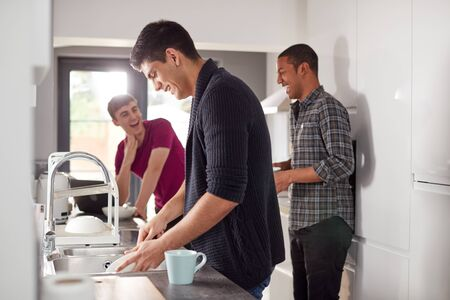 Group Of Male College Students In Shared House Kitchen Washing Up And Hanging Out Together