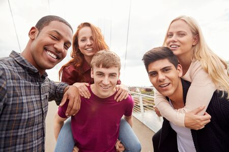 Outdoor Portrait Of Student Friends With Men Giving Women Piggyback Rides