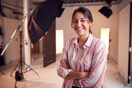 Portrait Of Smiling Female Photographer Standing In Studio With Lighting Equipment