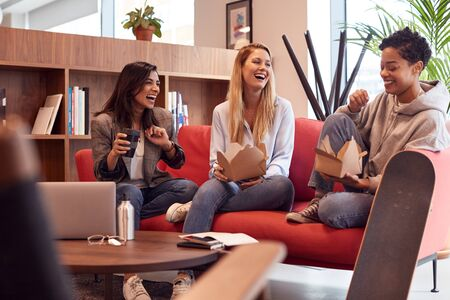 Group Of Young Businesswomen Sitting On Sofas In Open Plan Workspace Having Working Lunch Meeting