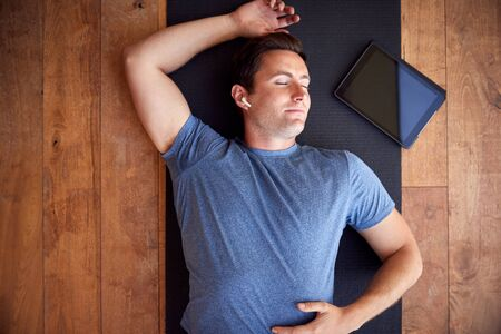 Overhead View Of Man Lying On Exercise Mat With Digital Tablet Listening To Wireless Headphones