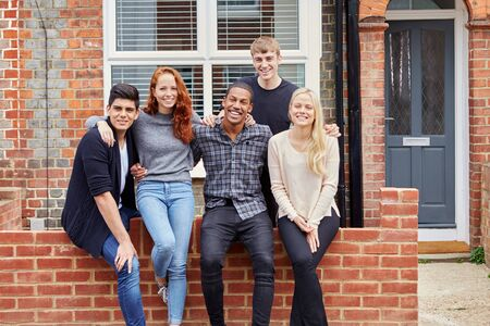 Portrait Of Group Of Smiling College Students Outside Rented Shared House 版權商用圖片