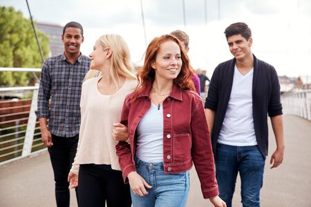 Group Of Student Friends Walking Across Bridge In City Together